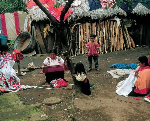 A woman kneels to weave, as a little girl looks on. Nabenchauk, 1991.